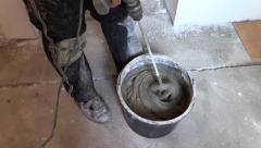 Worker mix adhesive cement for tile on bucket with tool Stock Footage