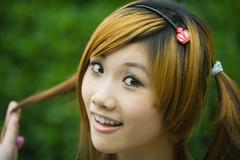 Young woman holding pigtail and smiling at camera, close-up, portrait Stock Photos