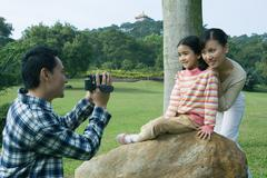 Man filming wife and daughter in park with video camera Stock Photos
