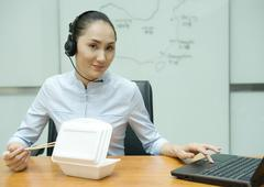 Businesswoman eating takeout food, wearing headset, and using laptop - stock photo