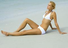 Woman in bikini sitting on beach - stock photo