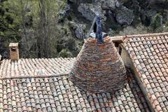 Conical chimney on a medieval tiled Stock Photos