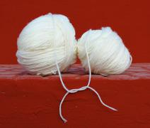 white wool balls tied up on red background - stock photo