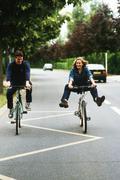 Couple riding bikes, woman doing trick Stock Photos