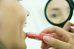 Teenage girl putting on lipstick, looking at self in hand mirror, cropped view - stock photo