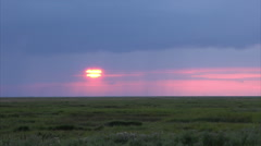 Sunset over river dee estuary marshes with rain on horizon, England Stock Footage