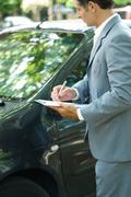 Mature man in suit inspecting car Stock Photos
