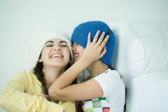 Two young female friends listening laughing Stock Photos
