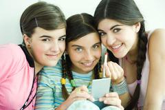 Three young female friends holding make-up, smiling at camera Stock Photos