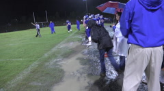 Mud soaked sideline with players during timeout Stock Footage