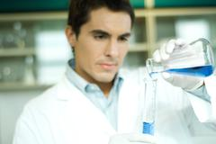 Male lab worker transferring solution from flask to graduated cylinder Stock Photos