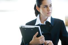 Young businesswoman holding binder, looking away Stock Photos