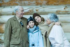 Teen and preteen girls with grandparents, standing in front of log cabin with - stock photo