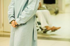 Patient standing with clasped hands, wearing hospital gown, cropped view - stock photo