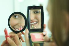 Two young friends putting on lipstick, looking at selves in hand mirrors, - stock photo