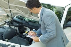 Mature man in suit inspecting car Stock Photos