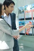 Couple standing next to window of real estate agency, looking at for rent and Stock Photos
