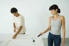 Stock Photo of Woman painting door with paint roller, man protecting woodwork with masking tape