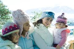 Three teen or preteen girls with toddler in mountains, all wearing winter coats - stock photo