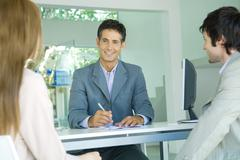 Young couple sitting across desk from smiling businessman, focus on businessman - stock photo
