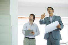 Two well-dressed men inspecting house, looking up - stock photo
