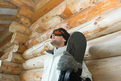 Young man with snowboard, leaning against log cabin, low angle view Stock Photos