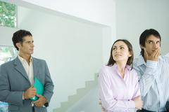 Real estate agent showing house to hesitant young couple Stock Photos