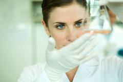 Female lab worker holding up flask Stock Photos