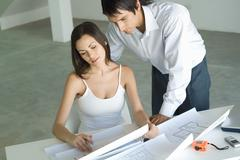 Couple looking at blueprints together, man looking over woman's shoulder Stock Photos