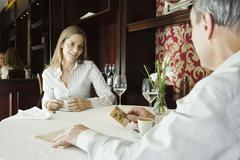 Mature couple having coffee in restaurant, man preparing to pay with credit card Stock Photos