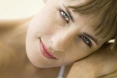 Woman smiling at camera, head resting on arm, portrait - stock photo