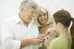 Young girl showing grandparents how to use MP3 player - stock photo