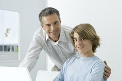 Father and son smiling at camera, man's arm around teenager's shoulder Stock Photos