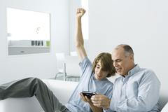 Teen boy showing handheld video game to father, arm raised Stock Photos