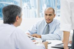 Businessmen having a meeting at desk, focus on man in background Stock Photos