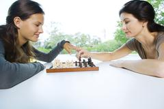 Two women playing chess, one making a move, the other touching her hand Stock Photos