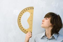 Young man holding up protractor, profile - stock photo