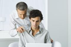 Mature man leaning over young man's shoulder, both looking at laptop computer - stock photo