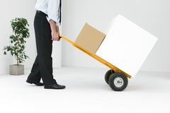 Businessman moving boxes with hand truck Stock Photos