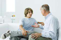 Father and teen son sitting together on sofa, having discussion - stock photo