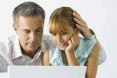 Father and daughter looking at laptop computer together, man's hand on girl's - stock photo