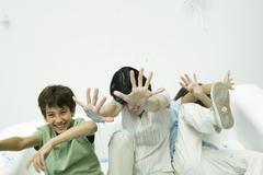 Stock Photo of Mother and two sons being sprayed with party string, laughing, hands raised