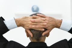 Business man with hands behind head looking at globe, rear view Stock Photos