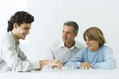 Mature father and two sons playing chess, all smiling Stock Photos