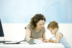 Stock Photo of Mother and toddler son drawing together at desk, open agenda nearby