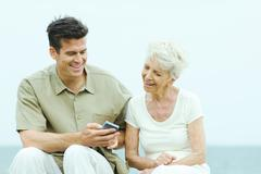 Senior woman with adult son looking at his wireless device - stock photo