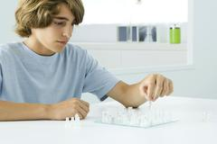 Teen boy sitting at table, playing chess - stock photo