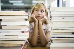 Young girl leaning on elbow daydreaming, stacks of books in foreground Stock Photos