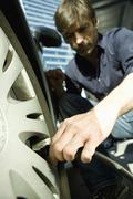 Man inflating vehicle tire using air pump hose Stock Photos