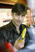 Stock Photo of Man at convenience store checkout counter buying snack